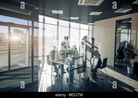 Panoramic view of male group of businessmen participating in hot disputes during negotiations with foreign partners, toned view through glass with sha - Stock Photo