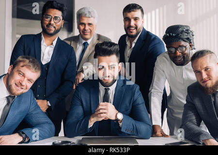 Multicultural business people including Arabic, Caucasian, Indian, Hispanic standing in modern office in group and looking confidently at camera. Conc - Stock Photo