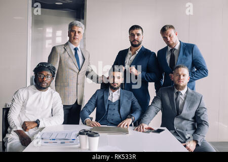 Confident multiethnic group of male business partners looking at camera while standing in a bright modern office with caucasian Executive sitting in m - Stock Photo
