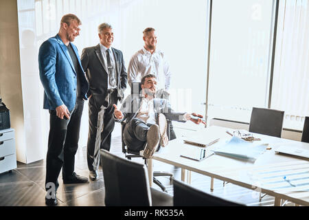 arrogant boss is sitting in the chair and talking with companions. copy space - Stock Photo