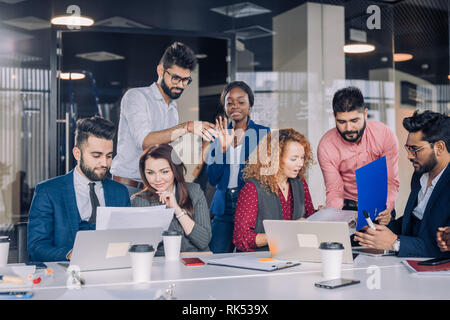 Woman showing coworkers something on laptop computer as they gather around a conference table - Stock Photo