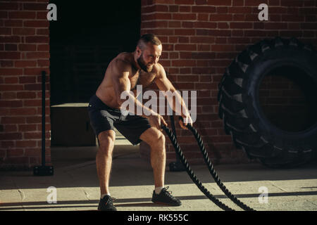 Athletic young man with battle rope doing exercise in functional training fitness gym. Rope helps engage all muscle groups at the same time, while ens - Stock Photo