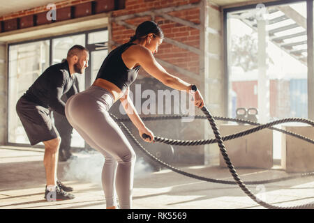 Caucasian fit couple exercising with battle ropes at gym. Woman and man dressed in sports outfit training together doing battling rope workout, with p - Stock Photo