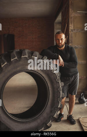 Professional CrossFit trainer explains principles of training with tire during functional workouts, leaning on the huge tire in street gym - Stock Photo