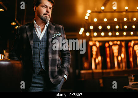 Portrait of wealthy prosperous senior art photographer in stylish bespoke suit posing near bar counter in the evening. - Stock Photo
