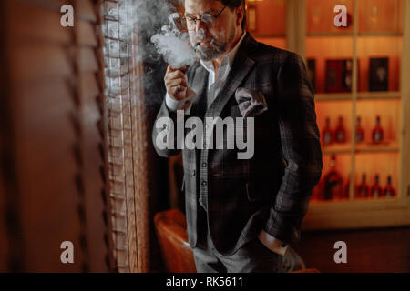 Confident pensive mature bearded male Business trainer in glasses smoking tobacco pipe, posing against cabinets with expensive wines, while visiting p - Stock Photo