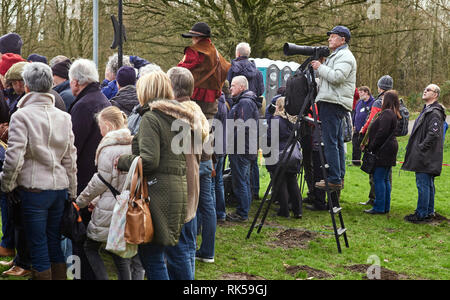 How a photographer deals with seeing over the heads of a crowd and having a long lens to support - Stock Photo