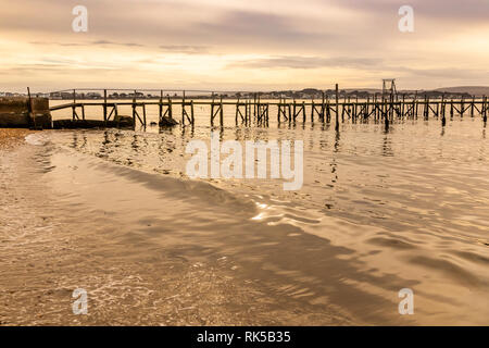 Colour landscape photograph taken on Poole harbour with gently lapping waves in foreground and silhouetted pier in background, Dorset, UK. - Stock Photo