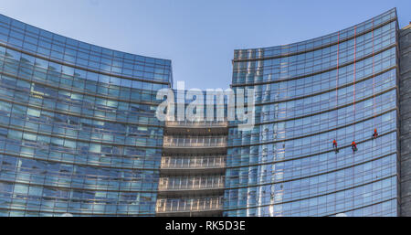 three workers work to clean the windows of a large skyscraper in Milan, men at work hooked on a double rope outside the building - Stock Photo