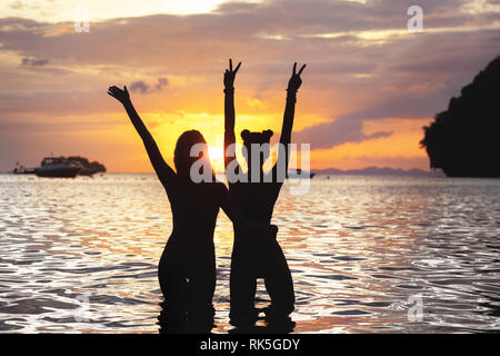 Two happy slim girls stands with raised arms at sunset sea beach - Stock Photo