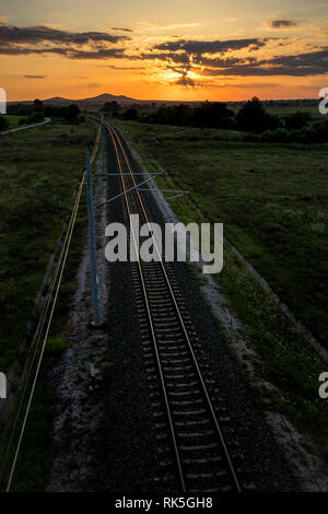 Long empty railway tracks as viewed from a bridge above at summer sunset behind clouds, dark colorful photograph taken near Krum, Bulgaria - Stock Photo
