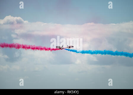 The Royal Air Force Red Arrows aeroplanes release smoke as they perform their routine at the Eastbourne Airshow in Sussex, UK. - Stock Photo