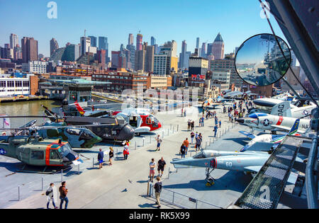 New York, NY / USA - 04.14.2018: NCY attraction Intrepid carrier ship deck with fighters and Manhattan skyscraper background - Stock Photo