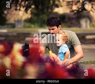Father and baby son are taking selfie outside in nature - Stock Photo