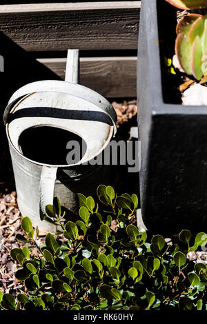 Old tin watering can sitting in the sun. - Stock Photo