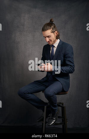Stylish handsome young man with long hair in a bun, wearing business suit, sitting on bar stool and looking at smartphone in his hands, texting. - Stock Photo