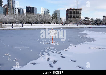 Bellevue, WA, USA. 9th Feb, 2019. The Downtown Park lake is frozen and emergency Keep Out signs are posted - Stock Photo