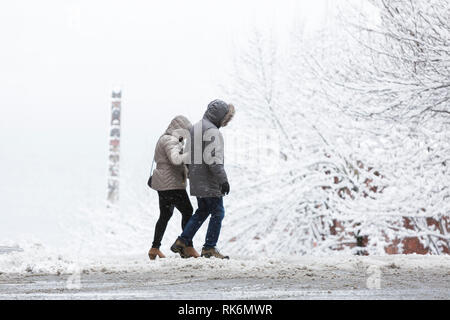 Washington, USA. 9th Feb 2019. A couple crosses Virginia Street as a strong winter storm blankets Seattle in six inches of snow. In the distance is a cedar totem from Victor Steinbrueck Park. Credit: Paul Christian Gordon/Alamy Live News - Stock Photo