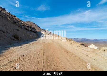 Dirt road leading along mountain side above valley below under bright blue sky with white clouds. - Stock Photo