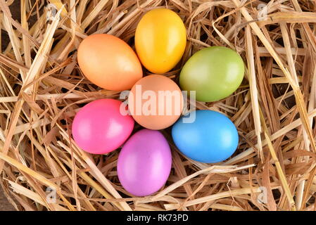 Colorful easter eggs on straw and wood planks - Stock Photo
