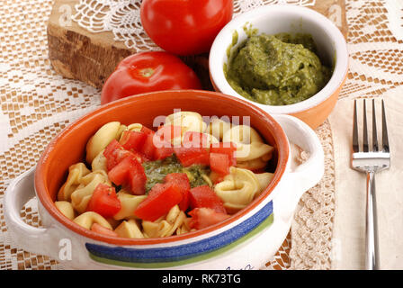 Tortellini with pesto and tomato on the table with embroidered tablecloth - Stock Photo