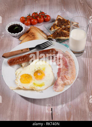 Breakfast with eggs and bacon in the pot on the table - Stock Photo