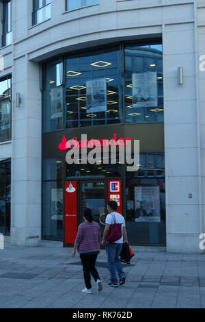 People walk past a branch of Santander bank in Frankfurt am Main, Germany. - Stock Photo