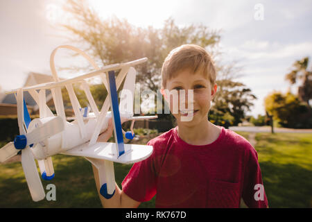 Happy young boy with a toy plane outdoors looking at camera. Preteen boy playing with his toy plane.