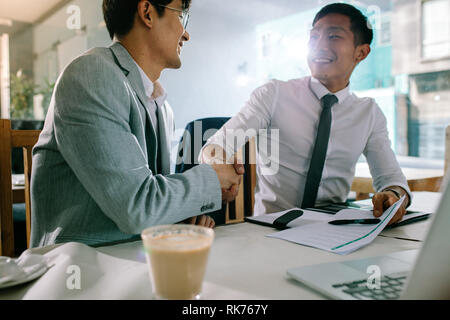 Two successful business men shaking hands with each other after a deal. Asian businesspeople sitting at coffee shop making a hand shake after a succes - Stock Photo