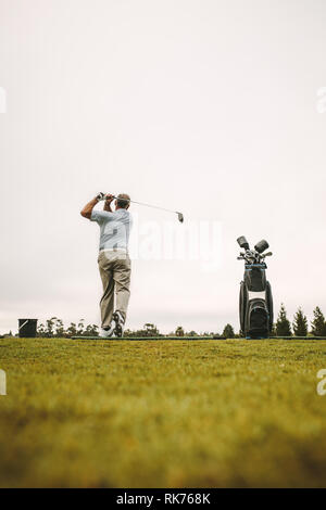 Senior man practicing his shots at driving range. Full length of senior male golfer practicing at golf course. - Stock Photo