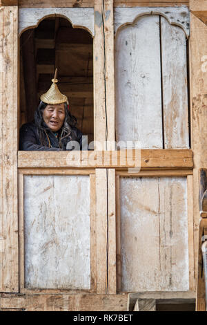 Old Layap woman at the window of her house in Laya, Gasa District, Snowman Trek, Bhutan - Stock Photo