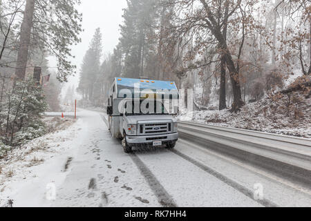 A RV driving on the road in Yosemite National Park during snowfall - Stock Photo