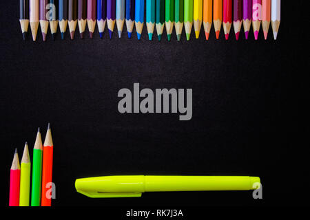 School and drawing supplies, on black background. Colored pencils, pencils and highlighter. With copy space. - Stock Photo
