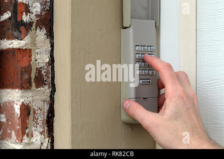 Hand enters code on keypad used on a garage door entrance to a home - security keypad - security code - Stock Photo