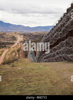 The U.S. - Mexico border near Nogales covered with multiple layers of concertina wire on the existing barrier wall February 5, 2019 in Nogales, Arizona. - Stock Photo