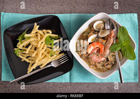 Pasta dish and plate with fish and seafood on the table - Stock Photo
