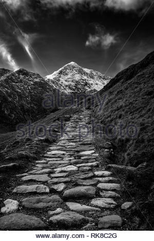 A  monochrome photograph of the Miners Path that leads up to the summit of the snow-capped Mount Snowdon - Stock Photo