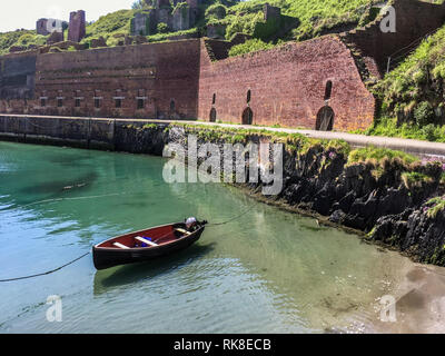 Quaint fishing village of Porthgain in Pembrokeshire with small moored boat in the tiny harbor. - Stock Photo