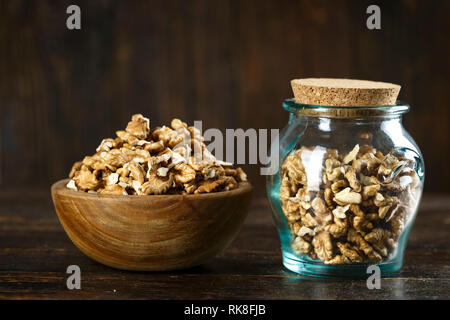 chopped walnuts on a table in a jar, on a brown wooden background. space for text - Stock Photo