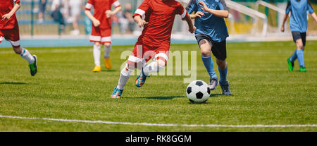 Football Soccer Players Running with Ball. Footballers Kicking Football Match. Young Soccer Players Running After the Ball. Kids in Soccer Red and Blu - Stock Photo