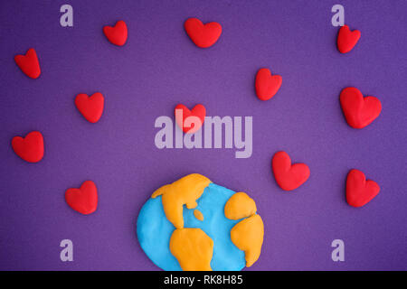 Planet Earth with red hearts. Planet Earth and Hearts are made out of play clay (plasticine). - Stock Photo