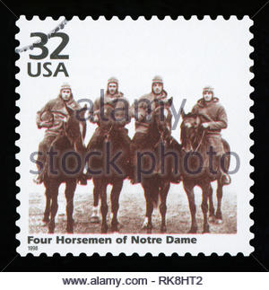 UNITED STATES OF AMERICA - CIRCA 1998: a postage stamp printed in USA showing an image of four players of Notre Dame Fighting Irish football team. - Stock Photo