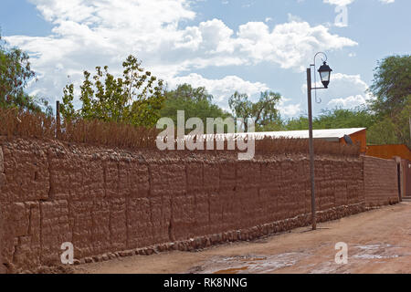 A street with puddles in San Pedro de Atacama after a rare rain in the desert, Chile. A street lamp at unpaved road and fence from red clay along it. - Stock Photo