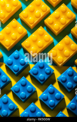 Plastic geometric cubes. Construction toys on geometric shapes paper multi colored background. Arranged in rows. Children's toy. Circle geometric shap - Stock Photo