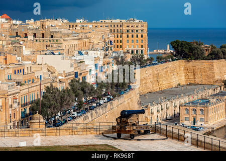 View of old cannon on bastion as city of Valletta on background. - Stock Photo