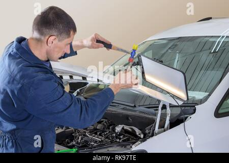 Professional mechanic removes dents on the car body - Stock Photo