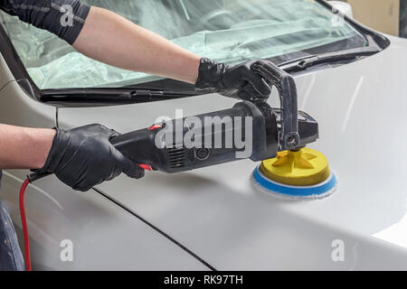 Man holds a polisher in the hand and polishes the car - Stock Photo