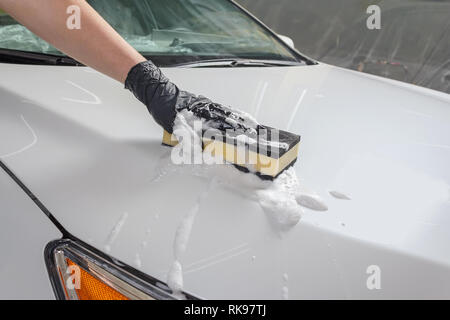 Car in the process of manual car wash with a yellow sponge and foam - Stock Photo