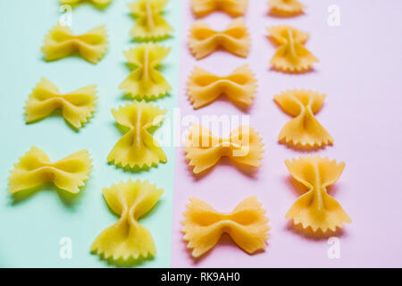 Bow tie Italian pasta fartalle pattern isolated on colorful background, top view. Dry uncooked macaroni concept. Pasta poster. Farfalle Pasta on pink - Stock Photo