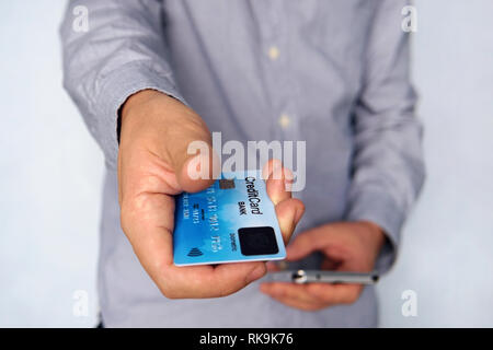 Cropped short of young man reaching out hand with blue credit card with fingerprint sensor and holding mobile in other hand. Businessman giving paymen - Stock Photo